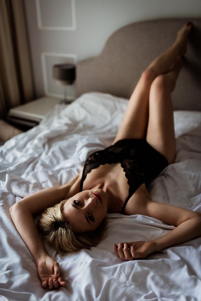 kobieta pozuje na łóżku w czarnej bieliźnie