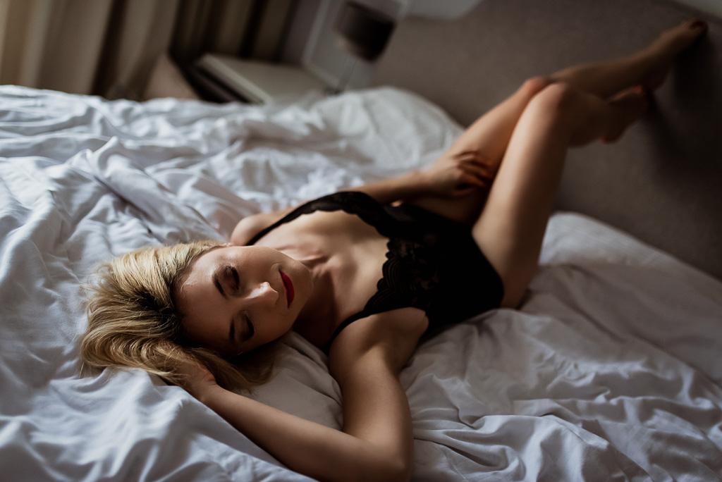 kobieta po 40stce blondynka pozuje na łóżku w czarnej bieliźnie