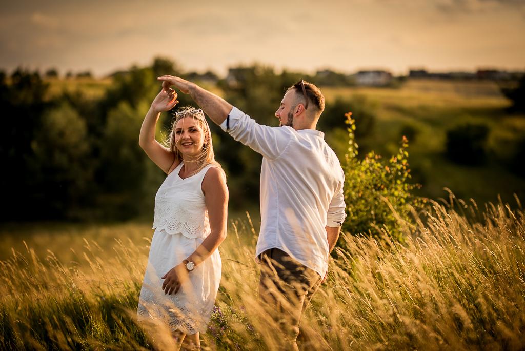 zakochani tańczą na łące o zachodzie słońca