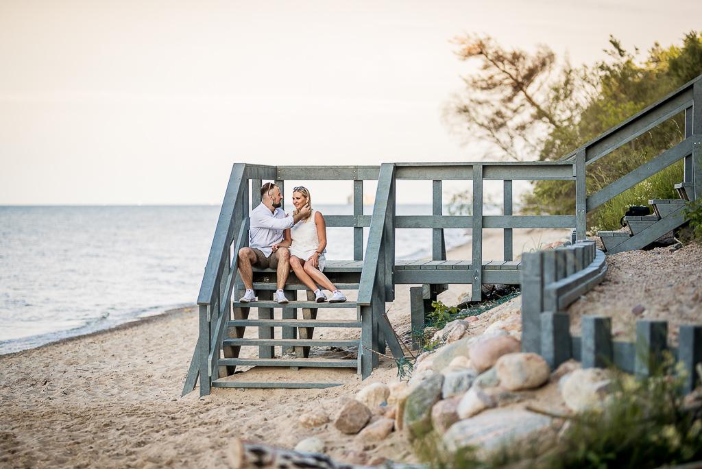zakochani siedzą na schodach na plaży
