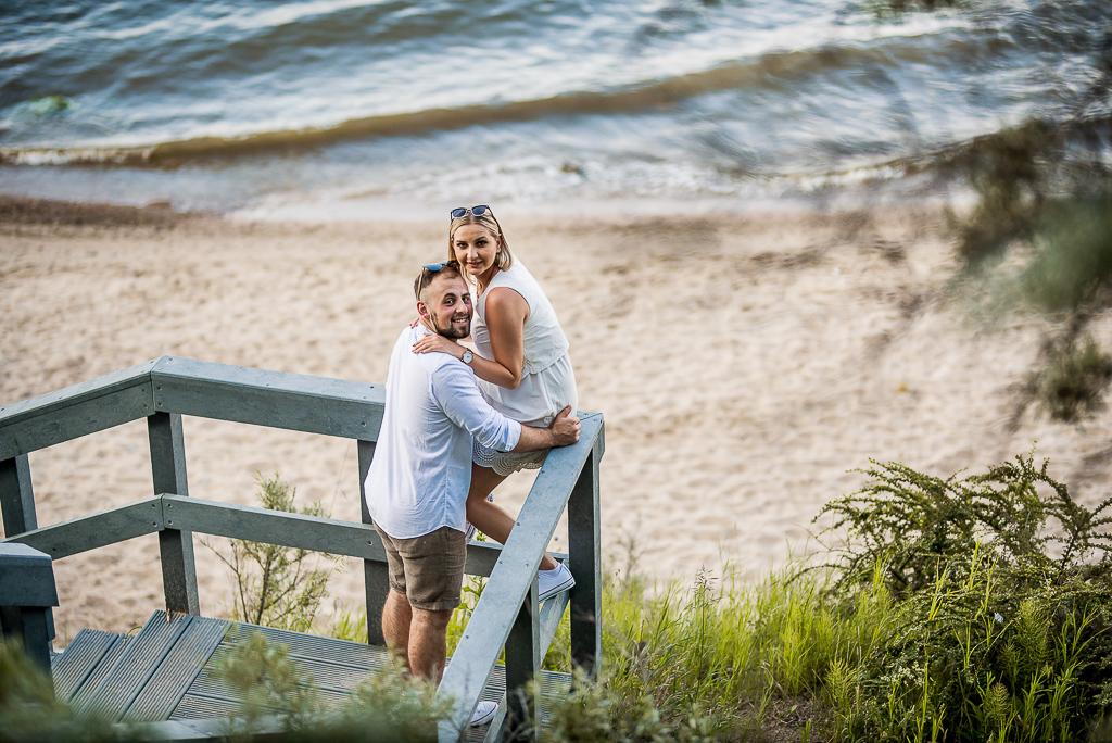 zakochani przytulają się na schodach na plaży