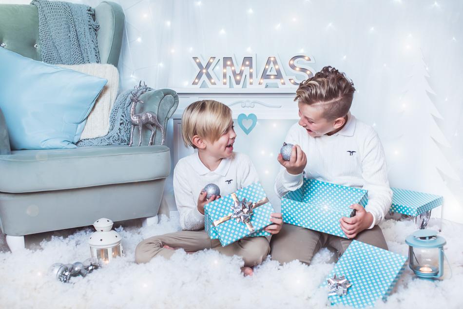 rodzeństwo bracia odpakowują prezenty na mini sesji zimowej świątecznej