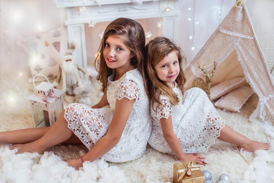 mini sesja boże narodzenie święta siostry na tle kominka biała sceneria