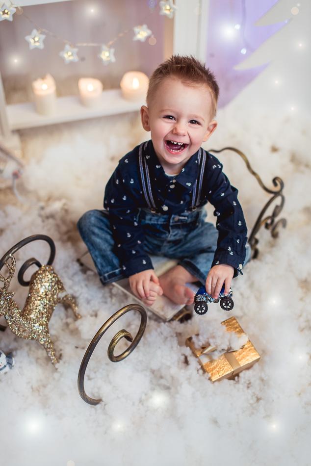 chłopiec siedzi na sankach odpakowuje prezent na mini sesji zimowej świątecznej
