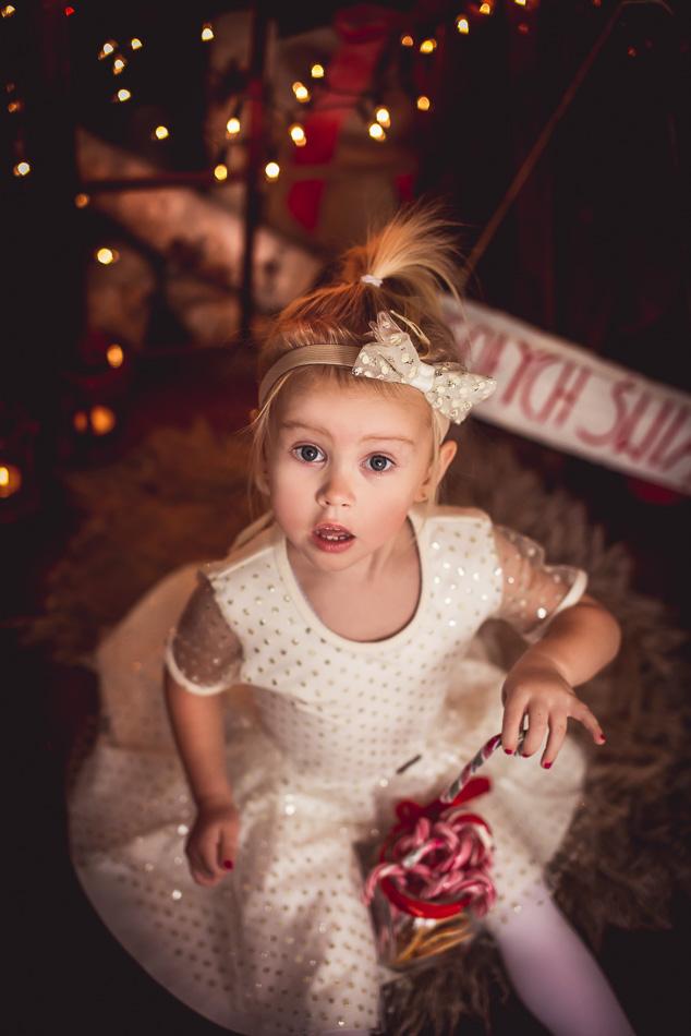 rodzeństwo dziewczynka odpakowuje prezenty na mini sesji zimowej świątecznej zdziwiona