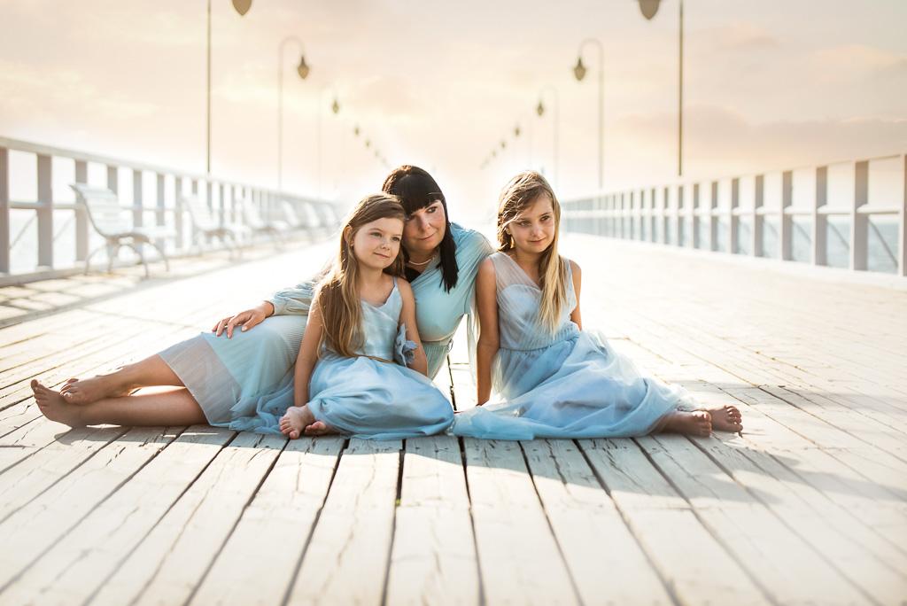 mama z córkami siedzi na na molo w Orłowie o wschodzie słońca
