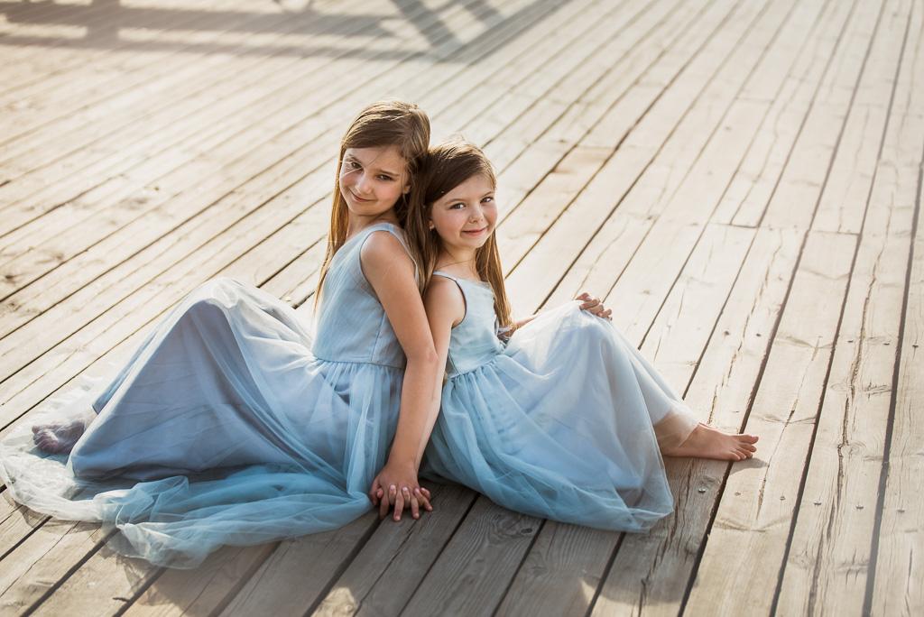 siostry siedzą na deskach molo ubrane w niebieskie pastelowe sukienki