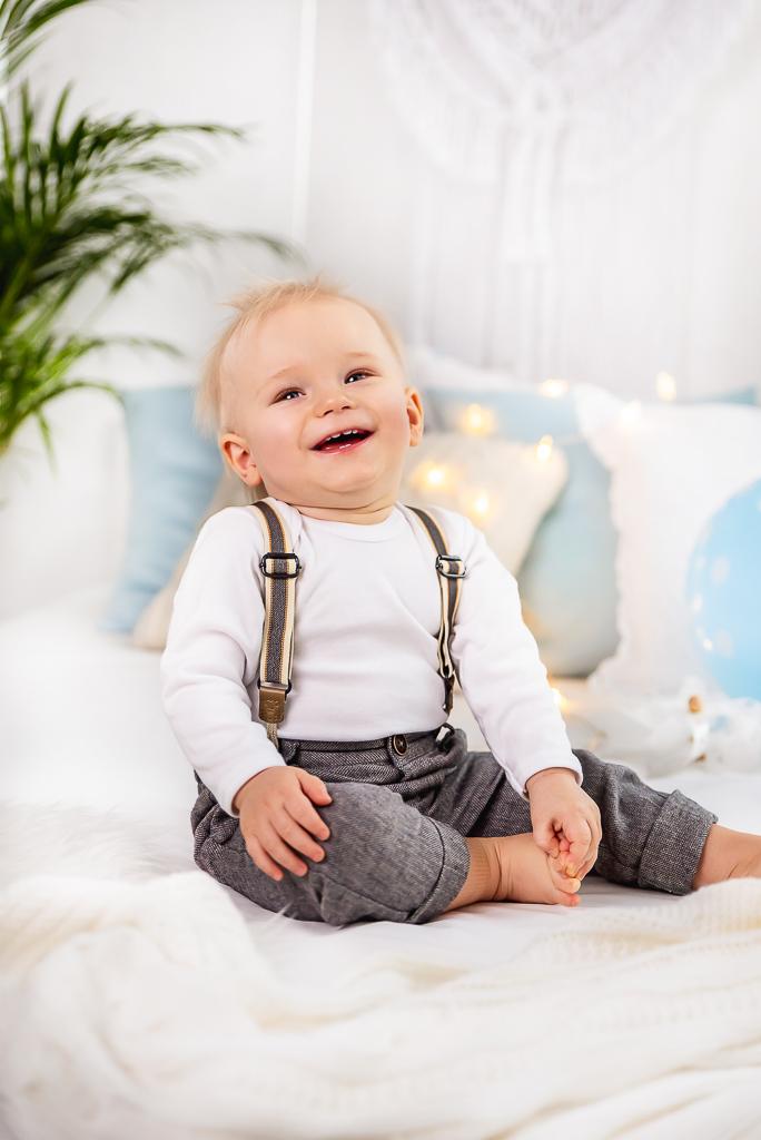 dziecko chłopczyk siedzi i uśmiecha się na łóżlu niebieskie dodatki