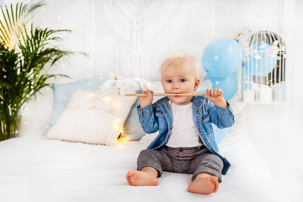 mały model siedzi na łóżku białe i niebieskie dodatki