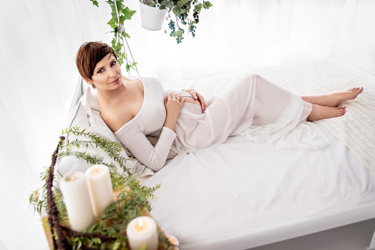 przyszła mama wśród świec i kwiatów na łóżku studio sesja ciażowa Trójmiasto