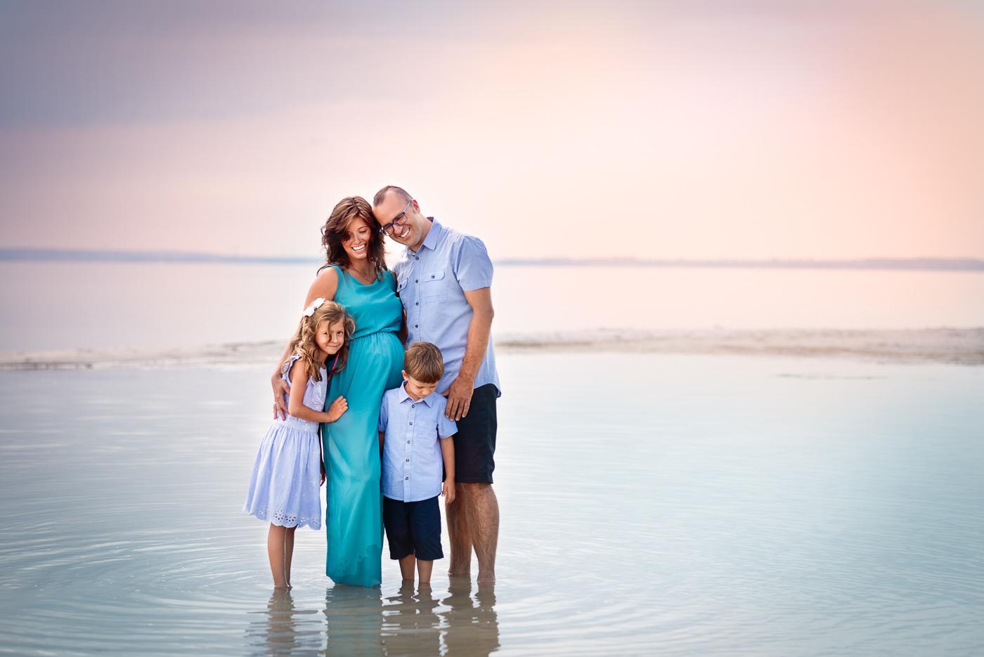 sesja zdjęciowa nad morzem o zachodzie słońca, mama tata, syn, córka stoją w wodzie na sesji, zdjecie Anita talaśka Fotografia