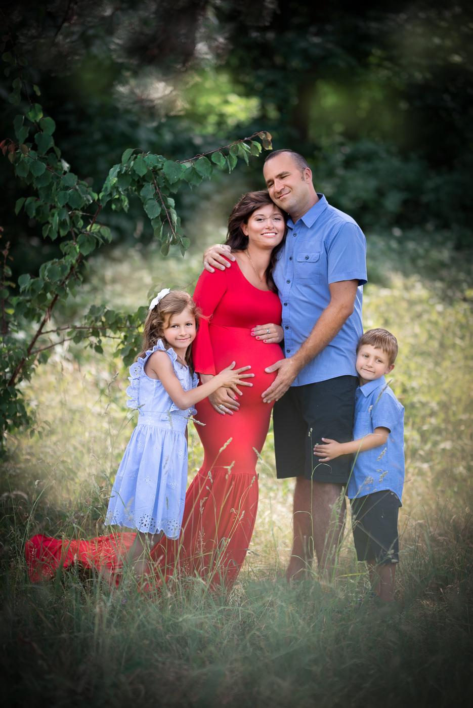 szczęśliwa rodzinka na sesji zdjeciowej w kolorach zieleni i błękitu w środku lasu
