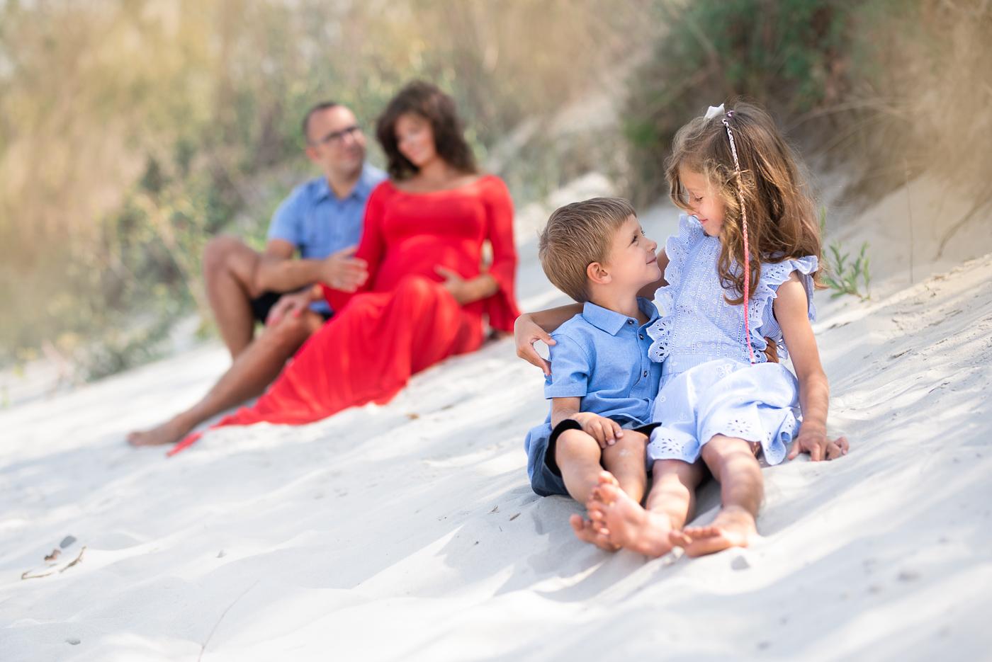 rodzieństwo sesja na plaży, brat z siostrą siedzą na piasku i się przytulają Trójmiasto