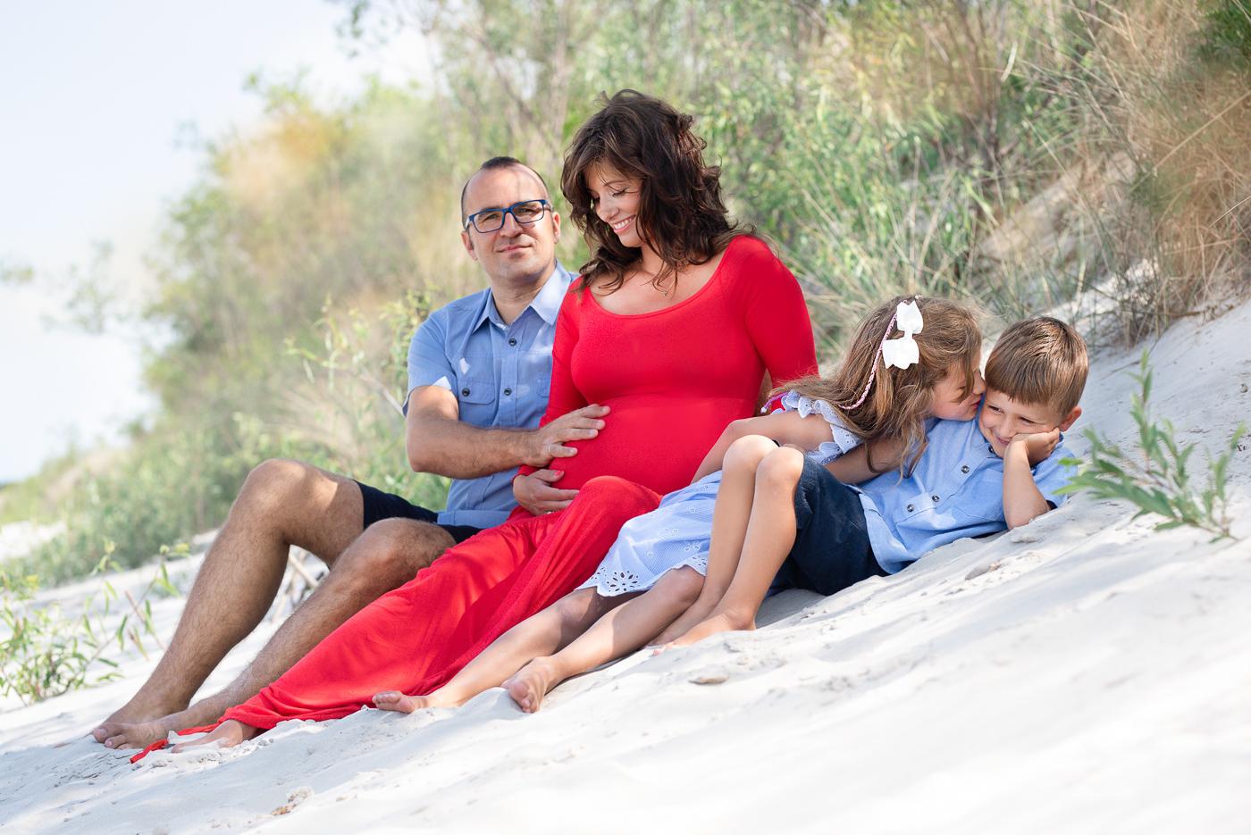 rodzina siedzi nad morzem na plaży w Helu, siostra całuje brata
