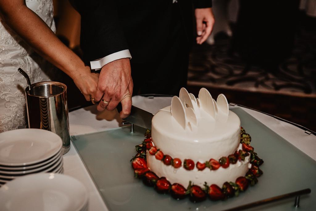 tort weselny para młoda kroi z owocami