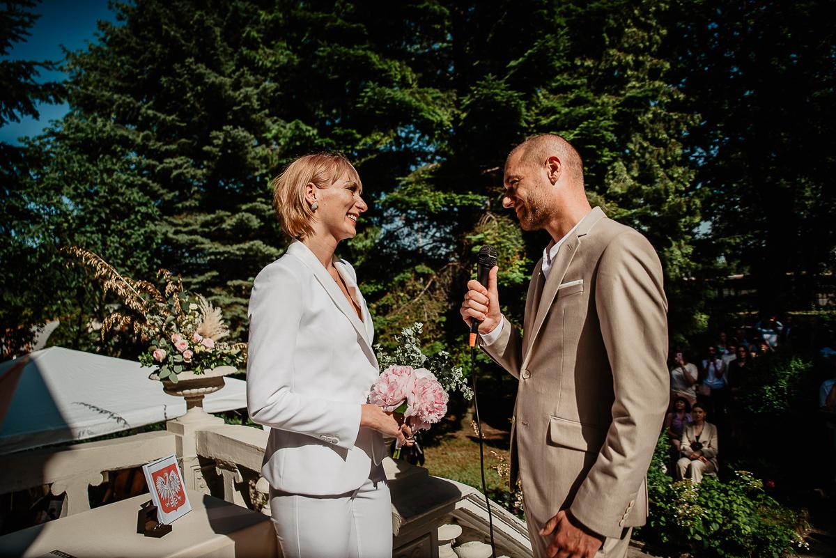 pan młody składa przysięgę na ceremonii ślubnej w plenerze