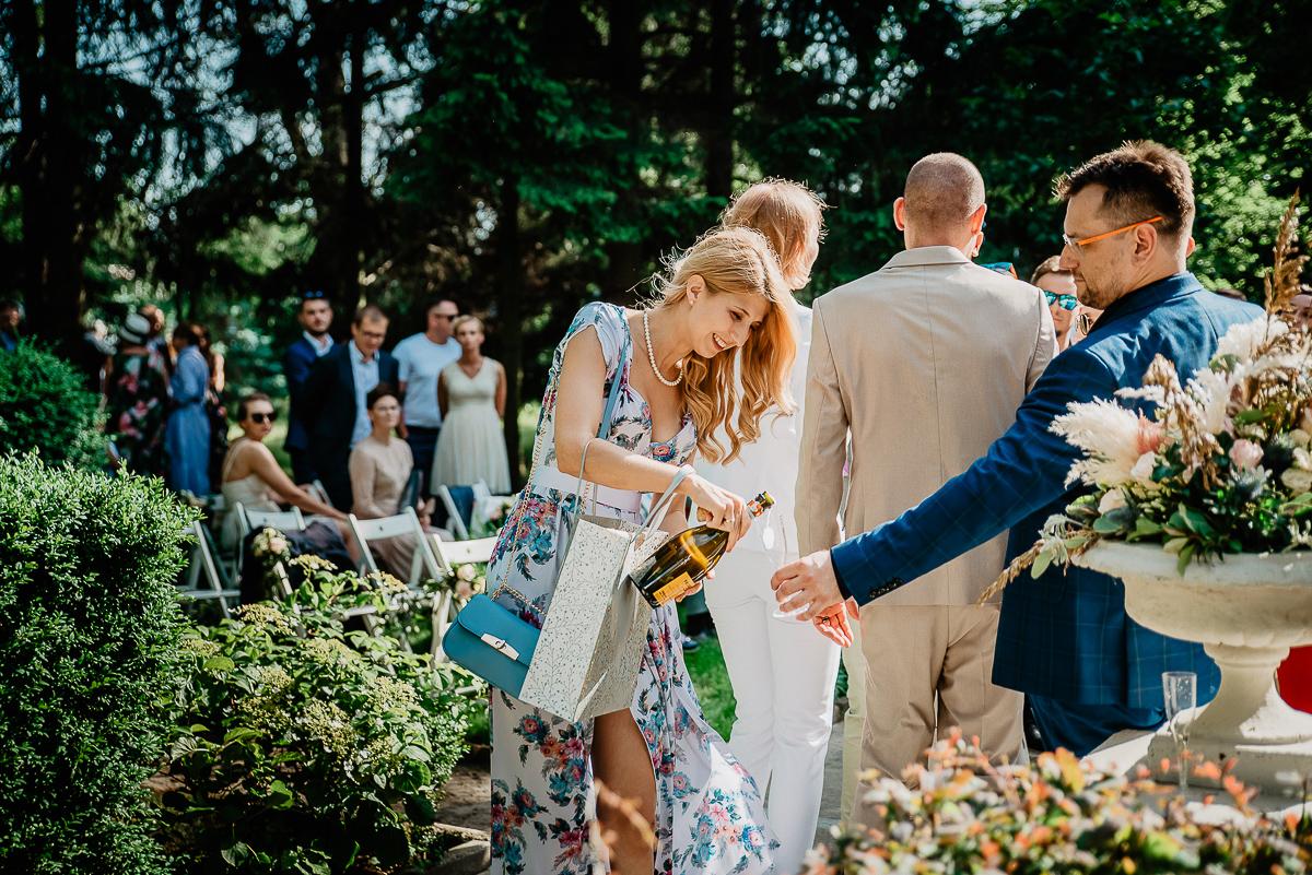 świadkowa otwiera prosecco na ślub w plenerze