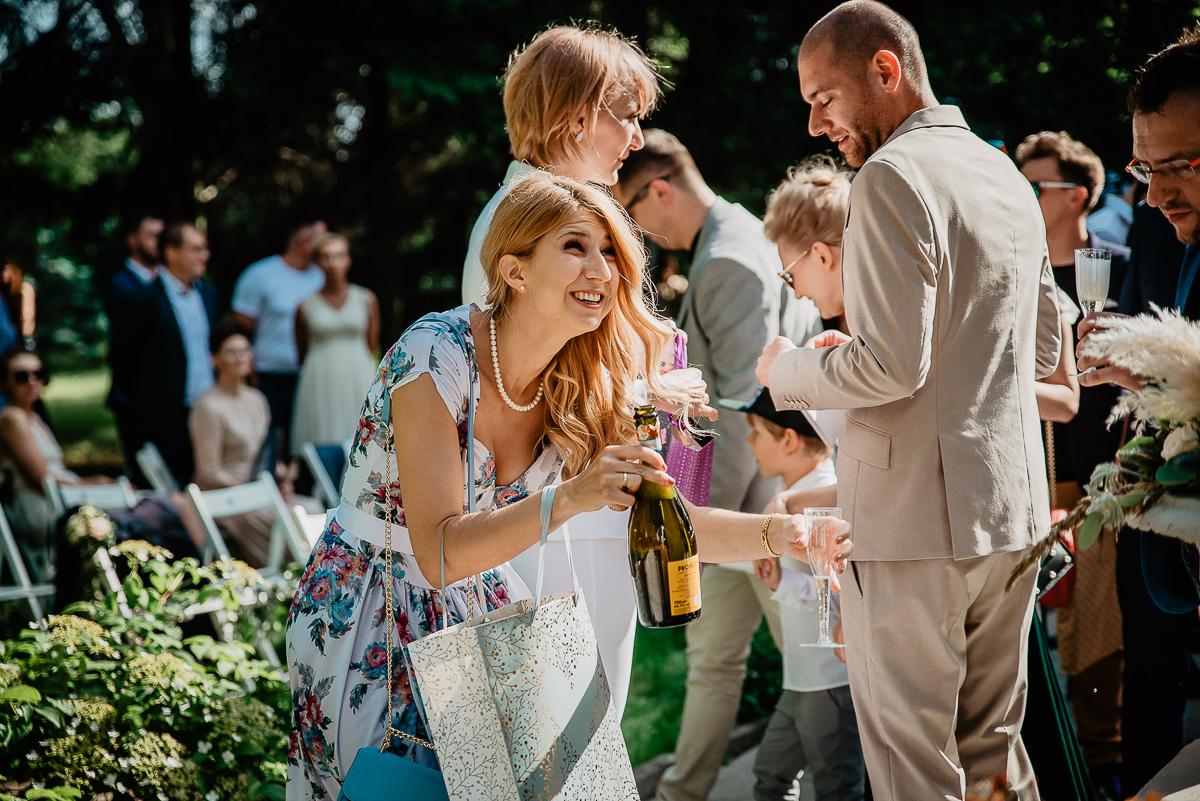 świadkowa ma sukienkę w kwiaty i otwiera prosecco na ślub w plenerze