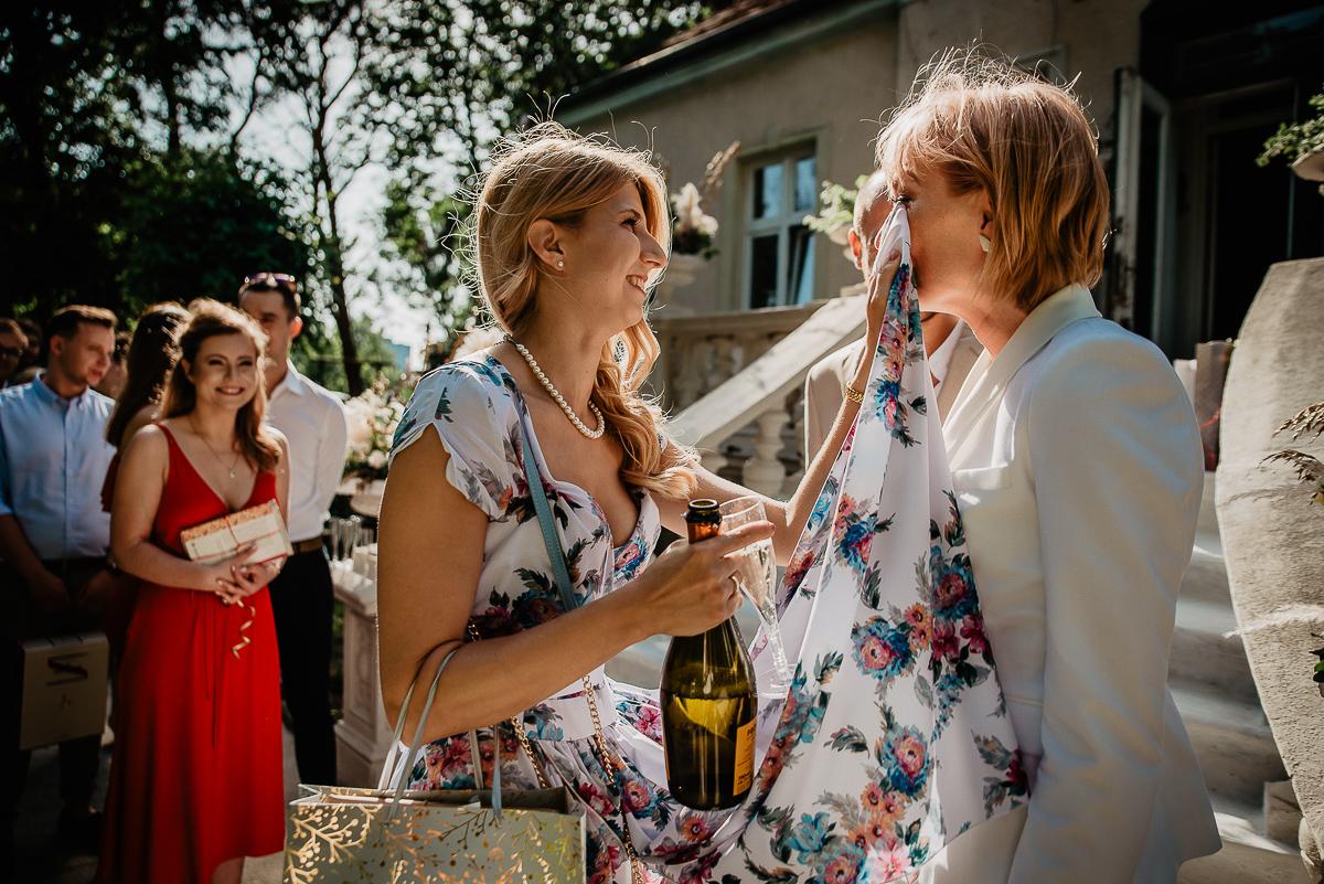 świadkowa ociera łzy pannie młodej ślub w Gdańsku w ogrodzie