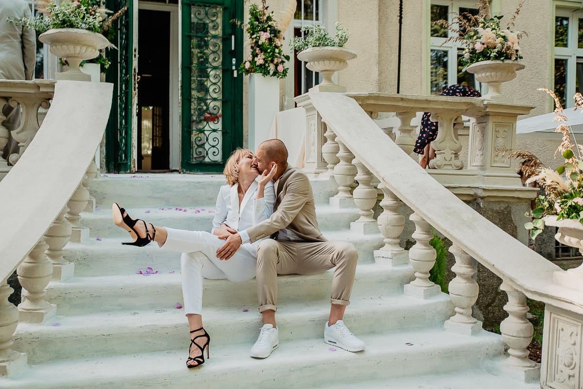 panna młoda w białym garniturze ślub w plenerze