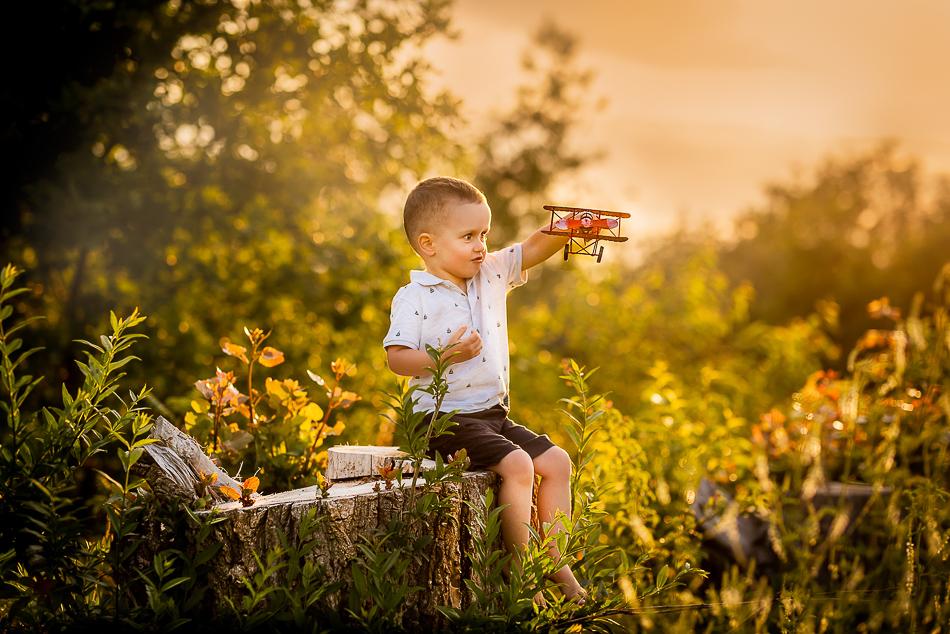 chłopiec z czerwonym samolotem podczas sesji rodzinnej