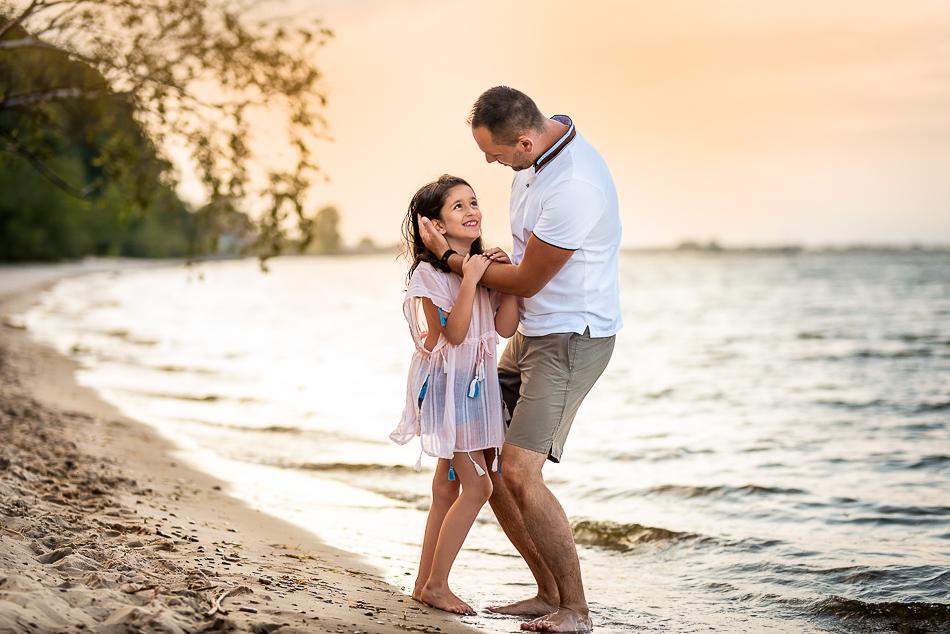 tata bawi się z córką na plaży