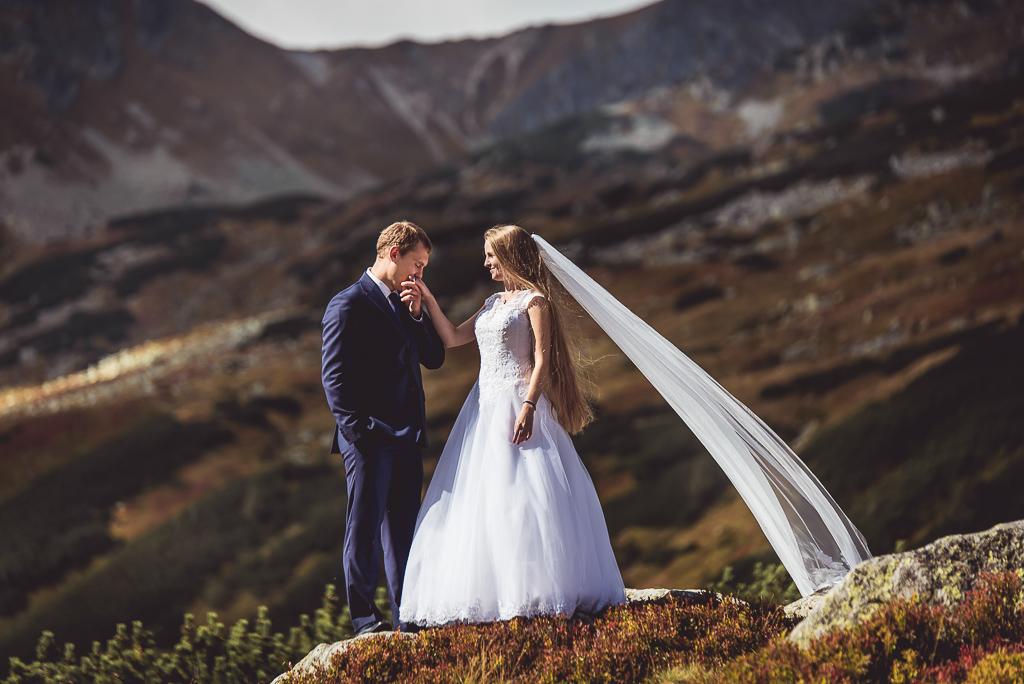 pan młody całuje rękę małżonki sesja w Tatrach